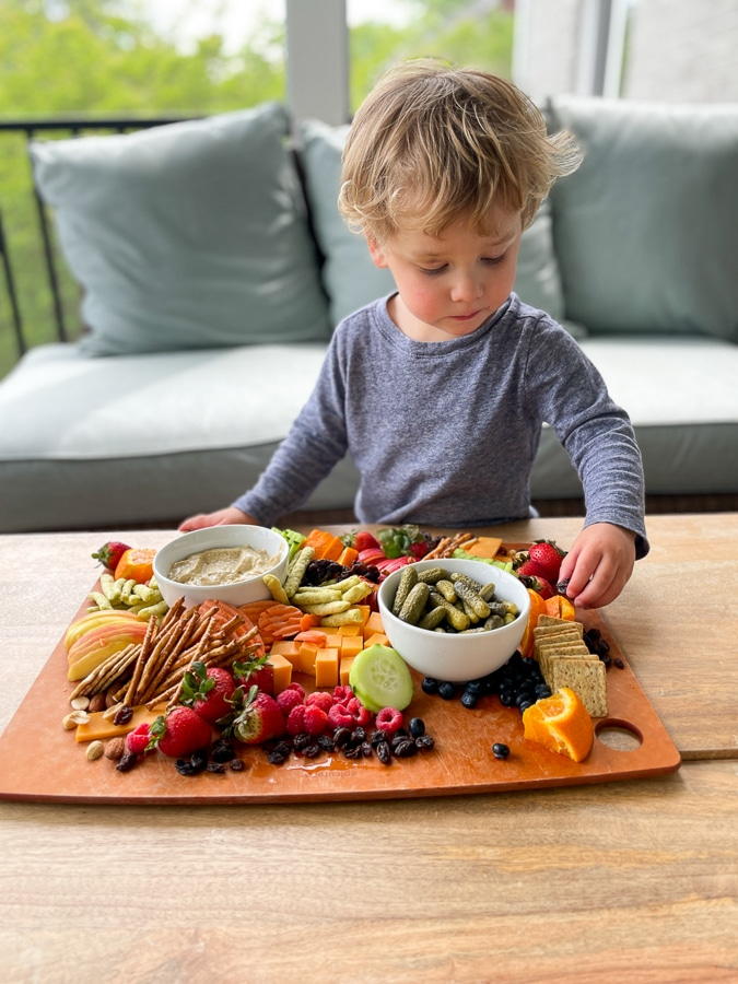 toddler reaching for Kids Charcuterie Board