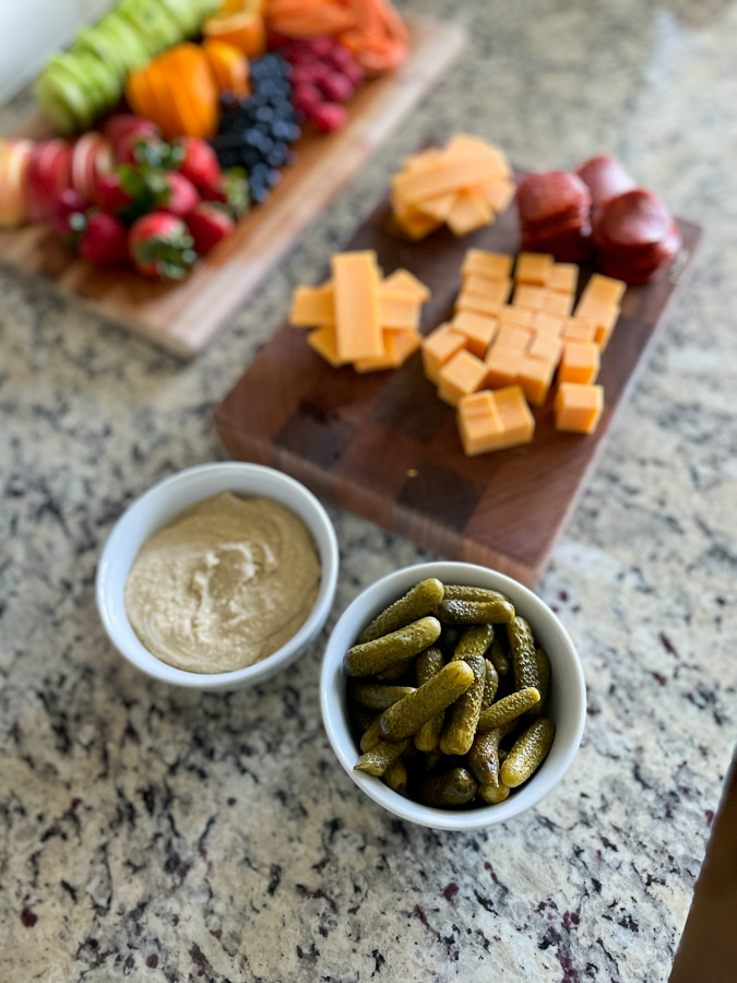Kids Charcuterie Boardprep with cheese, pickles and hummus in bowls