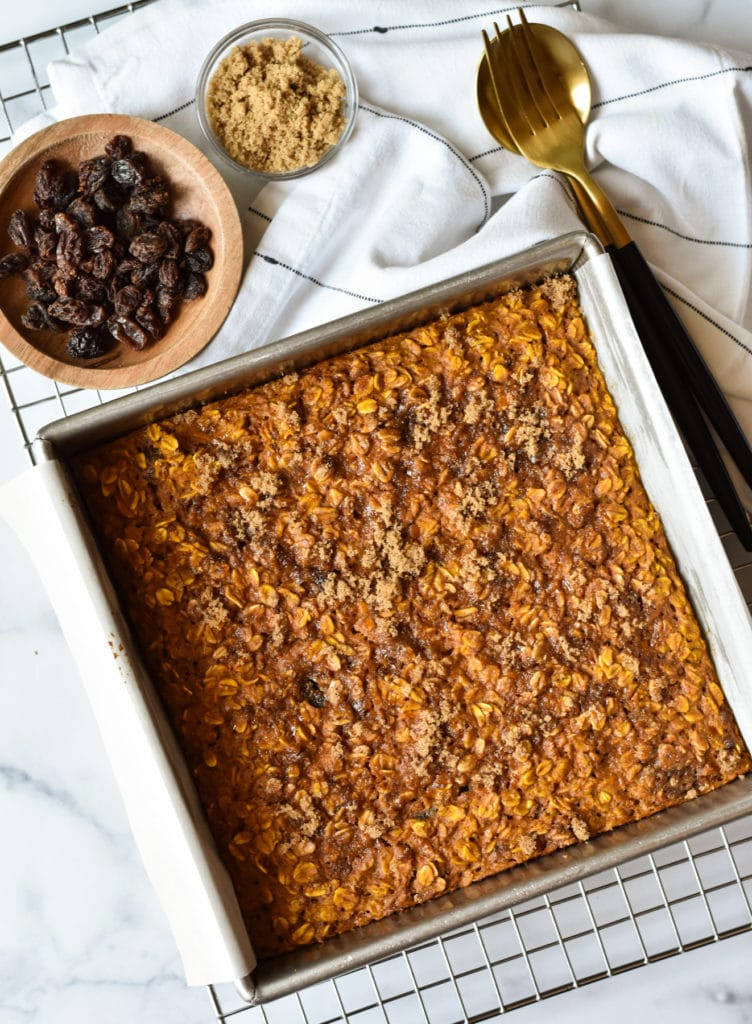 healthy baked oatmeal with pumpkin in a square pan with brown sugar and raisins on the side