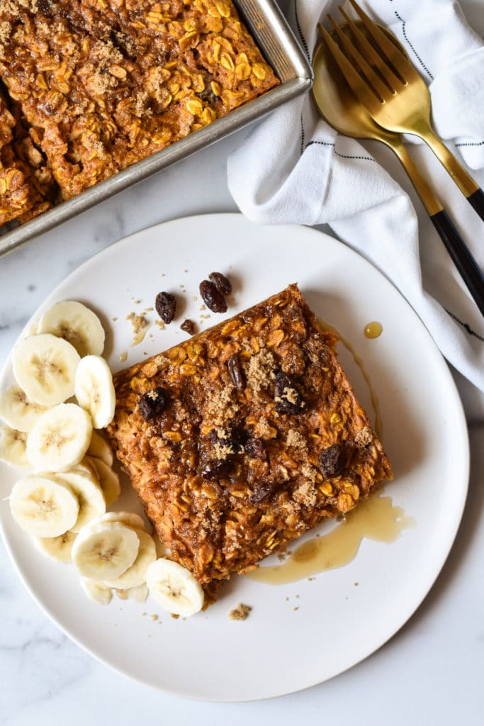pumpkin baked oatmeal square on a plate with banana slices and raisins