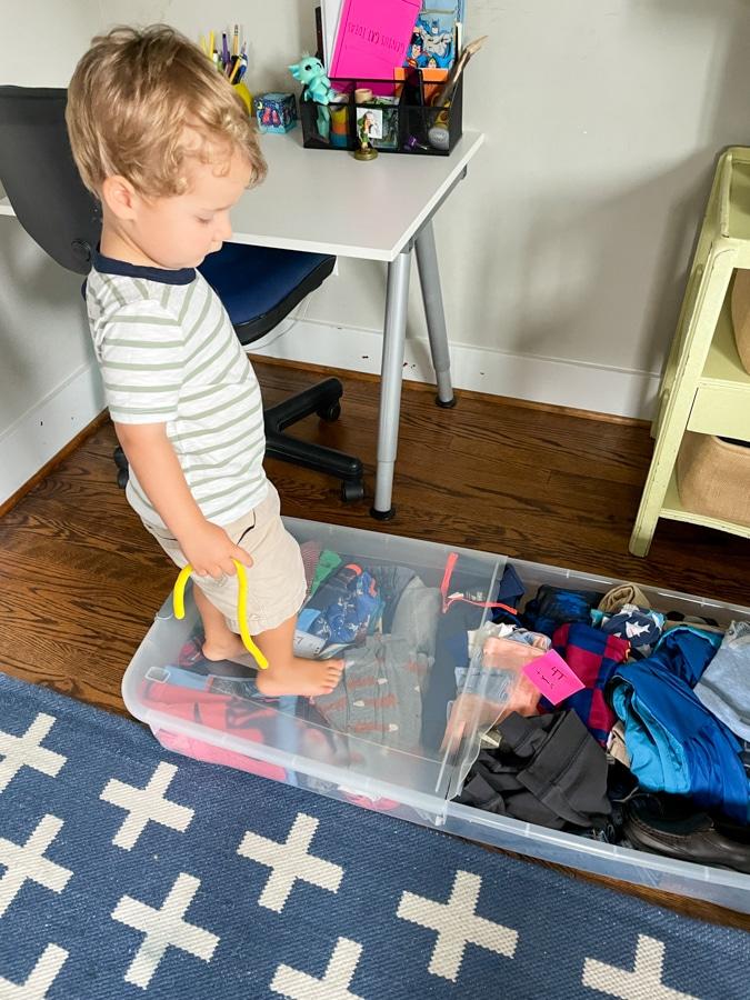 toddler standing on an underbed storage bin